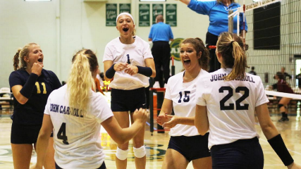 The Blue Streaks women's volleyball team celebrates after a 3–0 victory over Allegheny College.