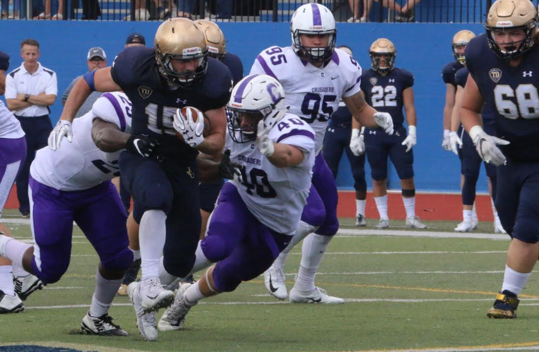 Sophomore running back Mike Canganelli (15) rushes through the Capital Crusaders defense on Oct. 6 at Don Shula Stadium.