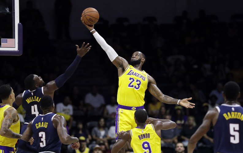 """""""Los Angeles Lakers forward LeBron James grabs a rebound over Denver Nuggets Paul Millsap during the first half of an NBA preseason basketball game on Sept. 30, 2018"""