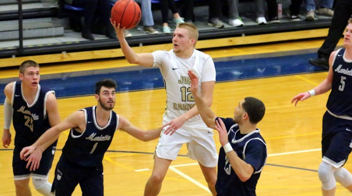 JCU+Sophomore+Luke+Hippler+%2812%29+goes+up+for+a+layup+between+two+Marietta+defenders%2C+successfully+scoring.+%28JCU+Sports+Information%29