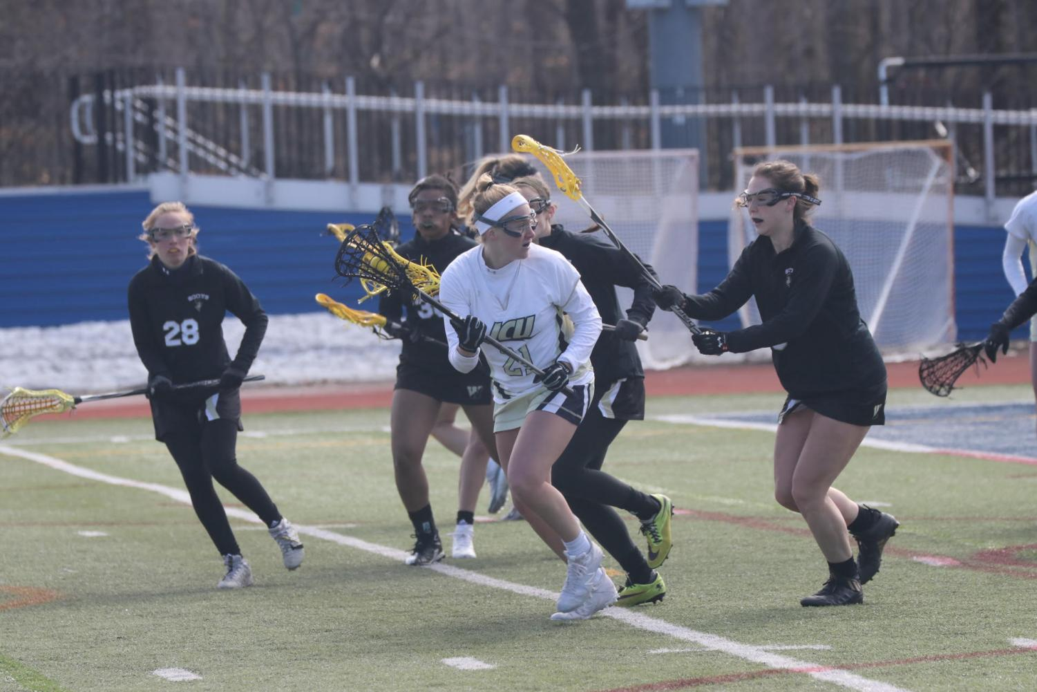 Sophomore midfielder Sophia Brandimarte looks to evade a flock of Wooster defenders in a game on Saturday afternoon on March 16 at Don Shula Stadium.