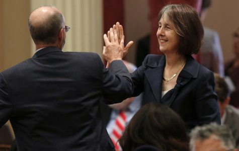 Sen. Nancy Skinner, D-Berkeley, and Sen. Steven Glazer, D-Orinda slap palms in celebration after her measure to let athletes at California colleges hire agents and sign endorsement deals was approved by the Senate in Sacramento, Calif., Wednesday, Sept. 11, 2019. The bill now goes to Gov. Gavin Newsom, who has not said whether he will sign it. (AP Photo/Rich Pedroncelli)