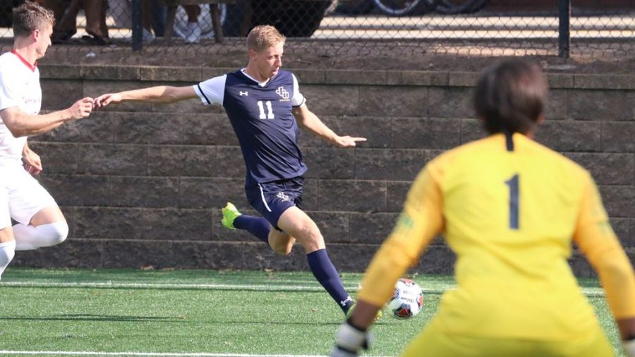 Junior midfielder Stephen Schutt (11) dials back for a shot on net in a game at Carnegie Mellon University in Pittsburgh on Sunday, Sept. 22, 2019.