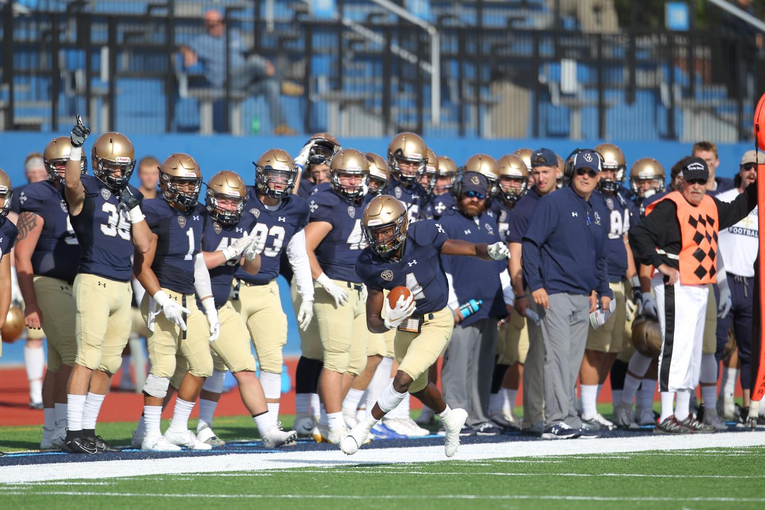 """Multiple records were shattered as the John Carroll Blue Streak football team routed the Capital Crusaders 90-0 at Bernlohr Stadium in Bexley, Ohio, last Saturday, Oct. 12.    The result of the game marked the most points scored in any NCAA game this season and broke an Ohio Athletic Conference record along the way.   The 90 points also tied a school record, previously set on Sept. 28, 1929, when John Carroll defeated Valparaiso by the same score.  """"I am just really proud of our football team,"""" head coach Rick Finotti said after the game. """"Those guys, behind the scenes — after the Mount [Union] loss — people were second guessing our guys. They didn't take it personal. They just bonded together and went to work.   """"Like I tell my players all the time, you guys give me everything that I ask of you. Work ethic, you do a great job in the classroom, a great job in the community. Just keep putting your nose to the grindstone and it will work out.""""  The Blue Streaks scored 28 points in the first half and then scored 27 points within the first six minutes of the third quarter to establish a 45-0 lead. From there, the Blue and Gold backups and reserves scored an additional 45 points.  """"We always look at our offense as a working process. A working progress. We just keep getting better,"""" offensive coordinator Jeff Fink said. """"When we are taking care of the ball early. The guys started to click a little bit more. We got a couple steps better. We just keep getting better. That result was because of the work the guys have put in over the last five weeks to get better.""""  Most impressively, seven different Blue Streaks scored touchdowns, including four players that registered their first career score. Twenty-nine different players made a tackle on defense.     The scoring started after Tyshawn Jones recorded an interception early in the first quarter, setting up junior Michael Canganelli to score his first of three rushing touchdowns on the afternoon.    Big plays were a dime a doz"""