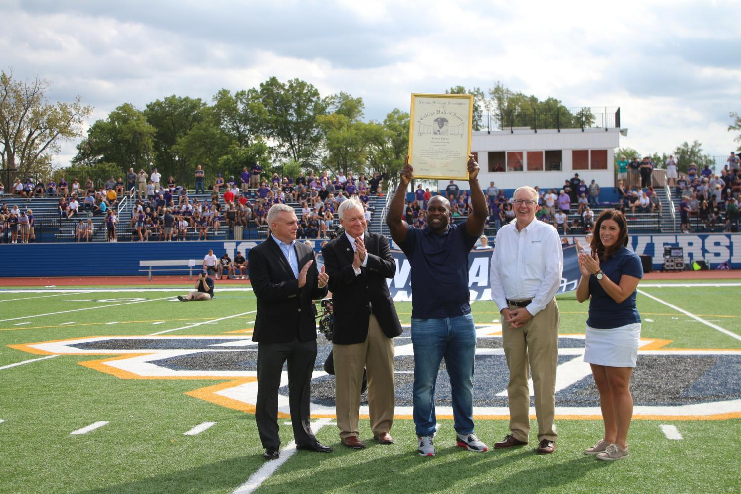 Pictured above is London Fletcher, showing his NFL Hall of Fame Plaque to the JCU crowd at halftime of the football game against Mount Union.(Photo by JCU Sports Information).