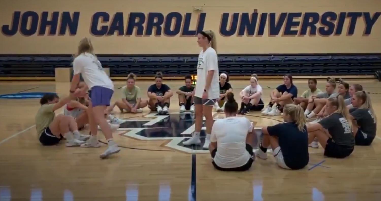 Junior Abby Adler picks up a teammate as senior Sarah Sprecher looks on in the DeCarlo Varsity Center.
