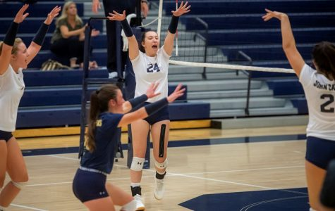 The JCU women's volleyball team celebrates after scoring a point in a game on the road during the 2019 season.