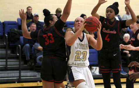 Junior Nicole Heffington [ball in hand] drives through the lane at the Tony DeCarlo Varsity Center during the JCU tip-off tournament.