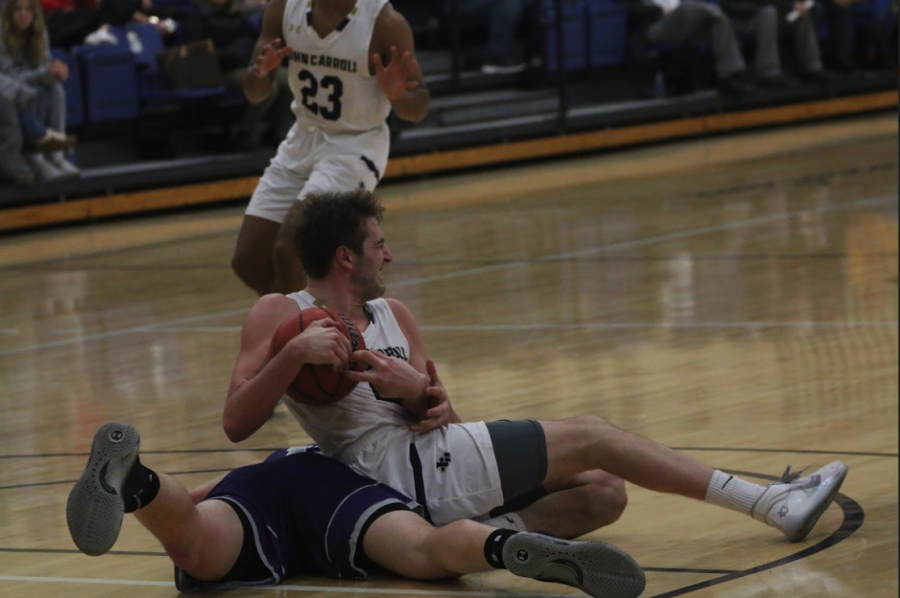 Senior Ryan Berer (ball in hand) tussles with a player from the Capital Crusaders in a game at the Tony DeCarlo Varsity Center.