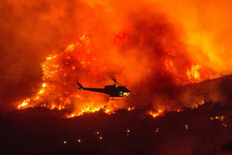 YUCAIPA, CALIF.  - In this Sept. 5 photo, a helicopter is seen preparing to drop water on a wildfire near Yucaipa, Calif., which was started by a pyrotechnical device used to reveal a baby's gender.