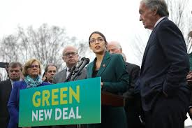 Representative Alexandria Ocasio-Cortez (center) speaks on the Green New Deal with Senator Ed Markey (right) in front of the Capitol Building in February 2019