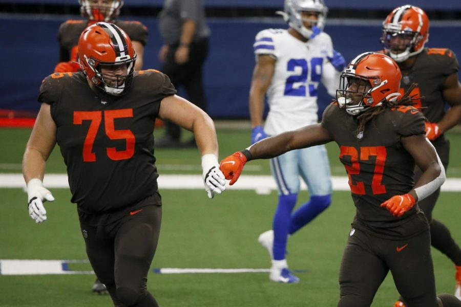 Cleveland Browns' Joel Bitonio (75) and Kareem Hunt (27) celebrate a touchdown run by Hunt in the second half of an NFL football game against the Dallas Cowboys in Arlington, Texas, Sunday, Oct. 4, 2020. (AP Photo/Michael Ainsworth)