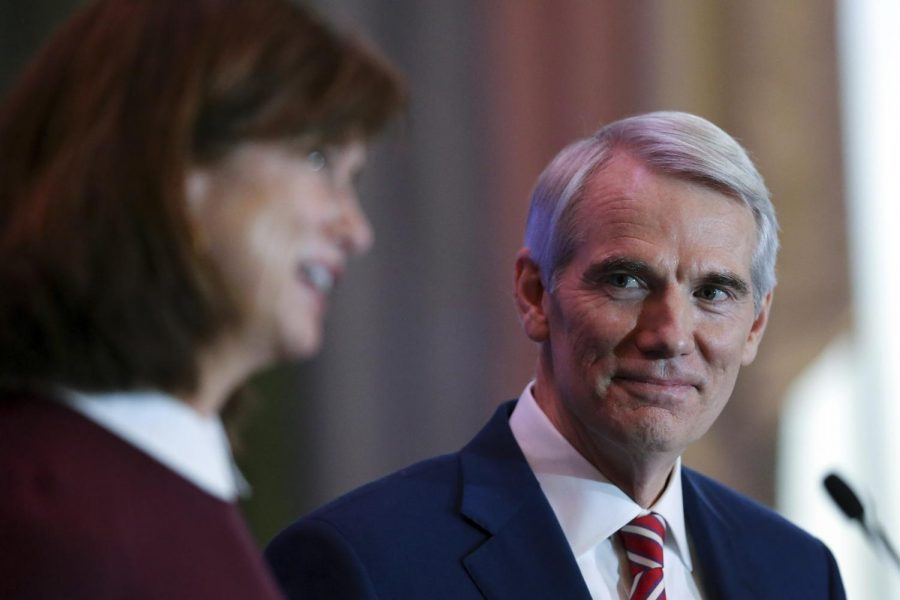 U.S. Sen. Rob Portman listens as his wife Jane answers a question after he announced Monday, Jan. 25, 2021, at the Hilton Hotel in Cincinnati, Ohio, that he will not be seeking re-election when his term is up in 2022. (Kareem Elgazzar/The Cincinnati Enquirer via AP)