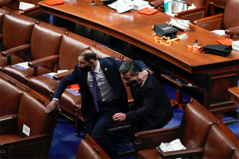 Lawmakers evacuate the floor as protesters try to break into the House Chamber at the U.S. Capitol on Wednesday, Jan. 6, 2021, in Washington.