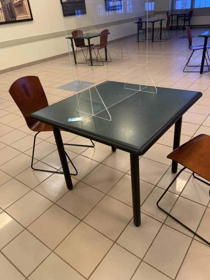 """Only two people are allowed to sit at each table, and this Plexiglass divider remains between them. The small blue card on the table displays a """"Clean"""" and """"Dirty"""" side that shows if a table has been sanitized since last use.  (Photo by Aiden Keenan)."""