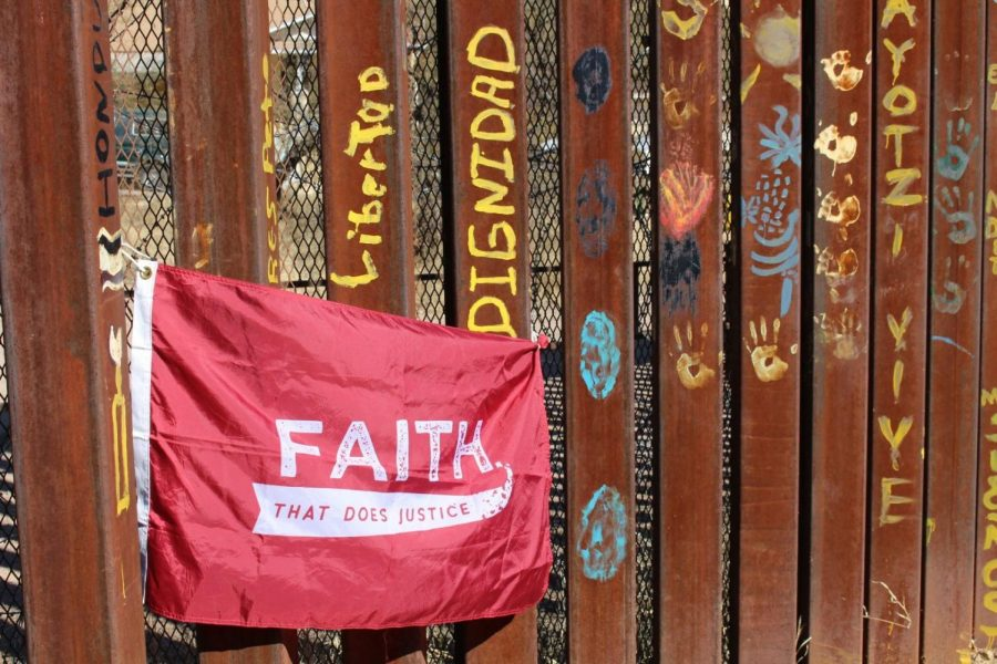 """A flag with Campus Ministry's central motto for immersion experiences, """"Faith That Does Justice,"""" hangs on the Mexican side of the border wall.  (Photo courtesy of Ray Flannery '22)."""