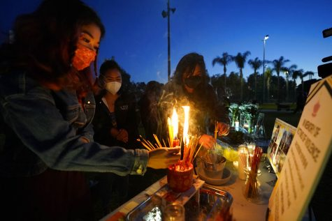 Women pay theirs respects at a memorial in honor of the victims of the shootings in Atlanta, where eight people were killed the week before, during a candle vigil in Monterrey Park, Calif., late Saturday, March 27, 2021.