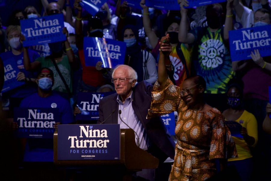 Sen. Sanders and Nina Turner hold their hands in the air on stage. (Photo by Aiden Keenan).