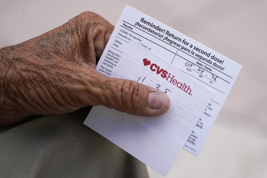 In this May 3, 2021 file photo, a man holds his vaccination reminder card after having received his first shot at a pop-up vaccination site.