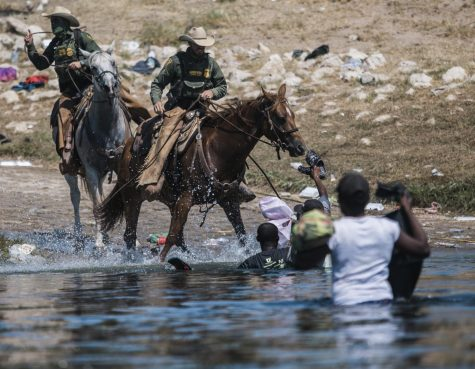In this Sept. 19, 2021, file photo, U.S. Customs and Border Protection mounted officers attempt to contain migrants as they cross the Rio Grande from Ciudad Acuña, Mexico, into Del Rio, Texas.