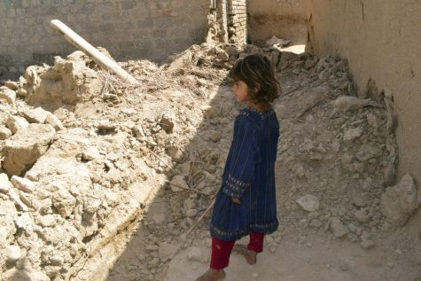 A girl looks at a damaged house following an earthquake in Harnai, about 100 kilometers (60 miles) east of Quetta, Pakistan, Thursday, Oct. 7, 2021.