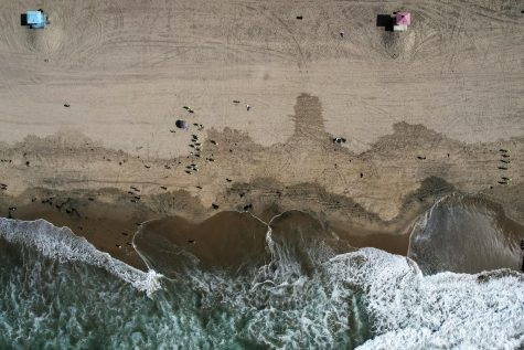 This Monday, Oct. 11, 2021, aerial file photo taken with a drone, shows beachgoers as workers in protective suits continue to clean the contaminated beach in Huntington Beach, Calif.