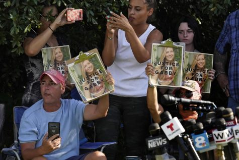 In this Wednesday, Oct. 20, 2021, file photo, Supporters of Gabby Petito hold up photos of Gabby after a news conference Wednesday, Oct. 20, 2021, in North Port, Fla. The FBI on Thursday, Oct. 21, 2021 identified human remains found in a Florida nature preserve as those of Brian Laundrie, a person of interest in the death of girlfriend Gabby Petito while the couple was on a cross-country road trip.