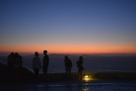 A sunset silhouetted by friends in Mykonos, Greece.